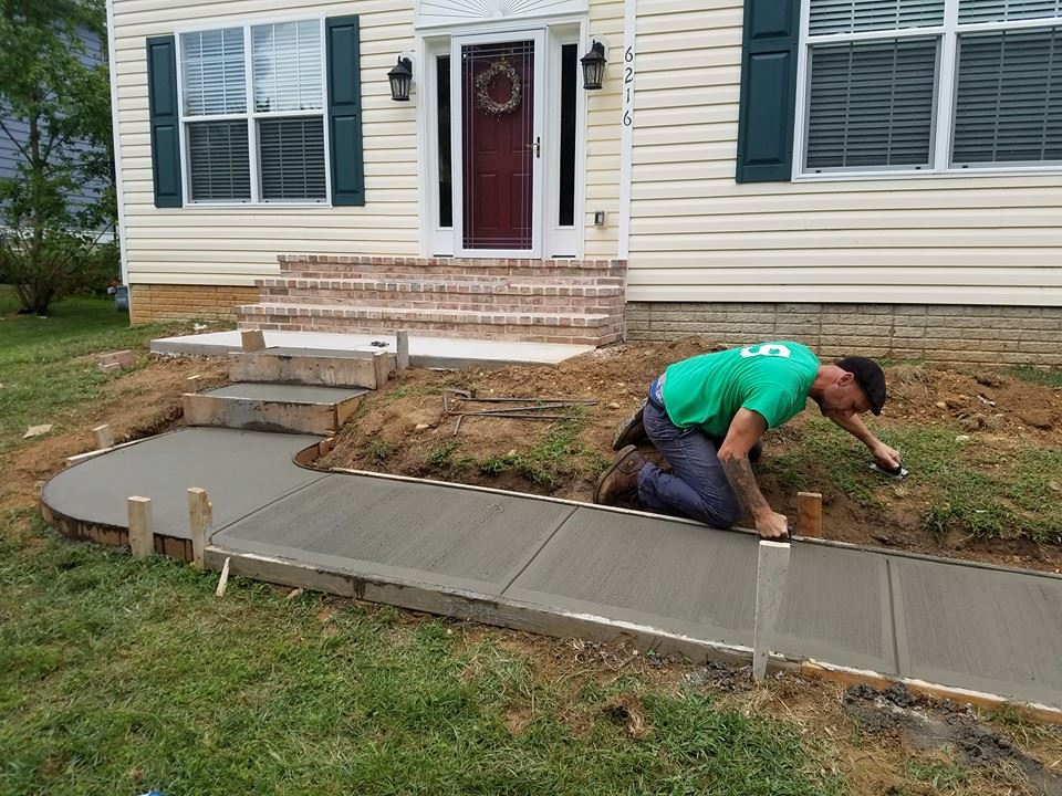 Finishing up the new sidewalk by hand.